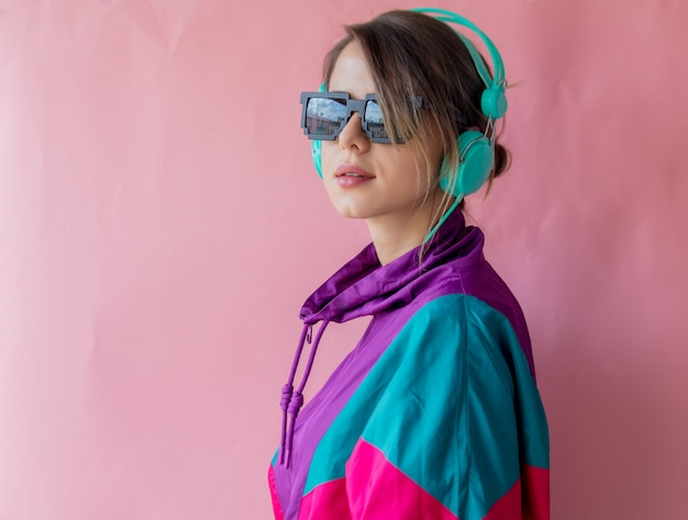 Young woman in 90s style clothes with headphones