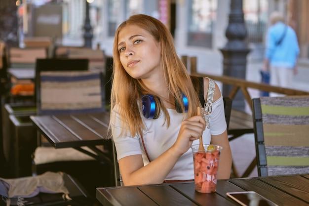 금발의 긴 머리와 이어폰을 가진 25 세 정도의 젊은 여성이 낮에는 거리 카페에 앉아 과일과 함께 디저트를 먹고 있습니다.