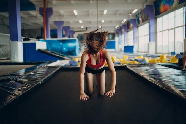 Молодая женщина-акробат прыгает на батуте.
