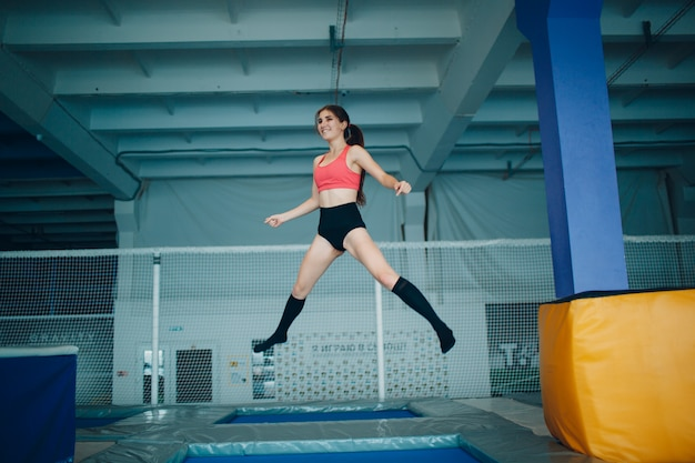 Young woman acrobat jumping on a trampoline