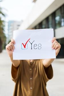 젊은 여성, 운동가는 찬성이라는 문구가 적힌 종이를 들고 투표를 요청합니다. 정치 활동, 선거 과정, 활동적인 삶의 위치 개념. 대통령, 헌법 선거.