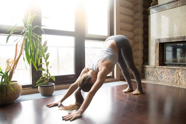 Young woman in adho mukha svanasana pose, home interior background