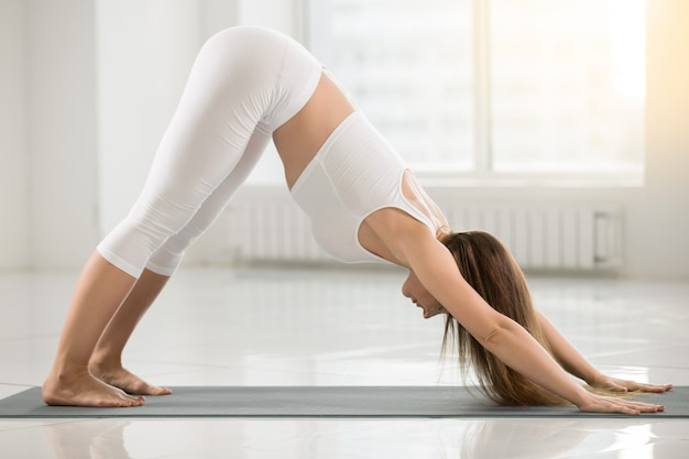Young woman in adho mukha svanasana pose, white color background Free Photo