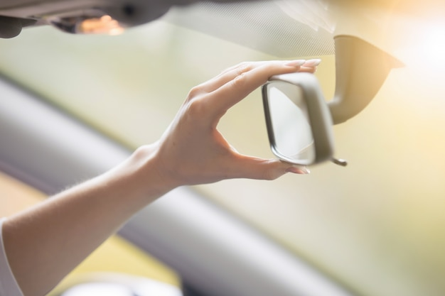 Young woman adjusting a rear-view mirror in the car