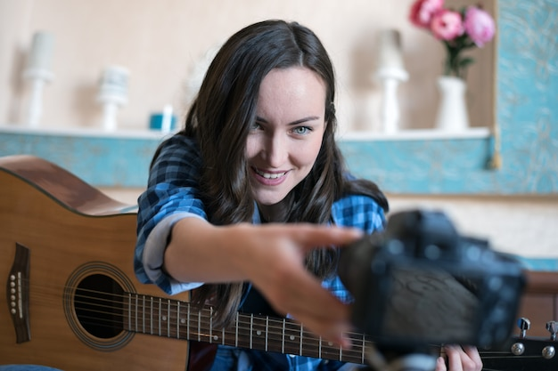 A young woman adjusts focus on the camera to record a music blog with guitar