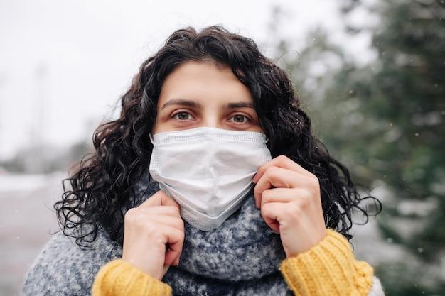 젊은 여자는 추운 서리가 내린 날에 겨울 눈 덮인 공원에서 의료 멸균 마스크를 조정합니다.