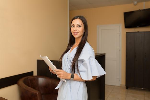 レセプションの若い女性管理者は論文とフォルダーを保持します。