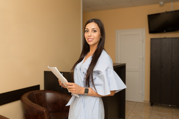 Young woman administrator on reception hold folder with papers