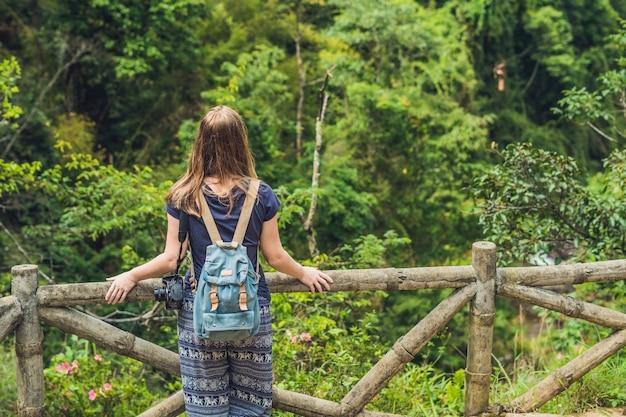若い女性は田舎のフェンスでベトナムの自然を賞賛します
