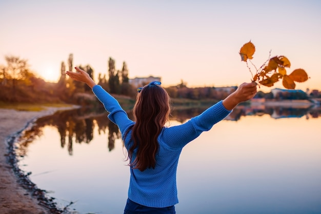 Young woman admiring autumn river with raised hands holding branches