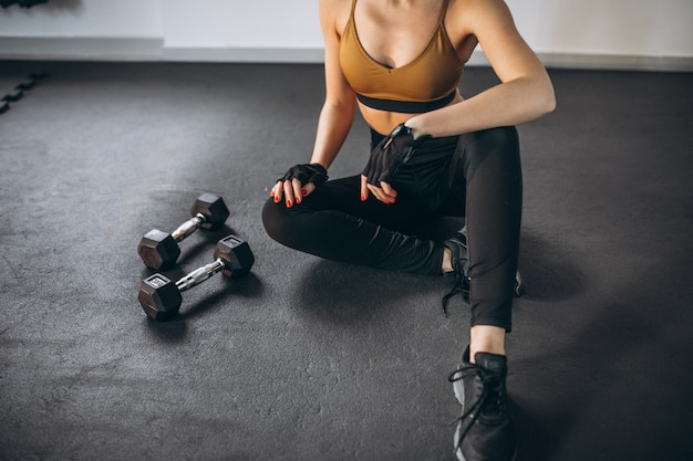 Young woman aercising at the gym with dumbbells