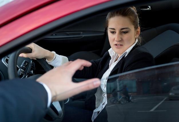 Молодая женщина боится грабителя, пытающегося ворваться в машину