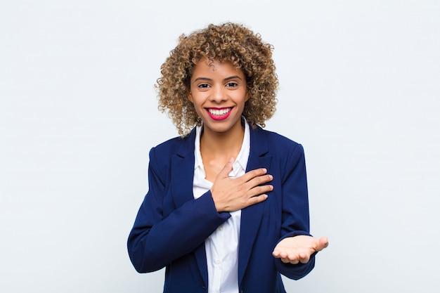 Молодая женщина-афроамериканка чувствует себя счастливой и влюбленной, улыбаясь, держа одну руку рядом с сердцем, а другую протягивая к плоской стене