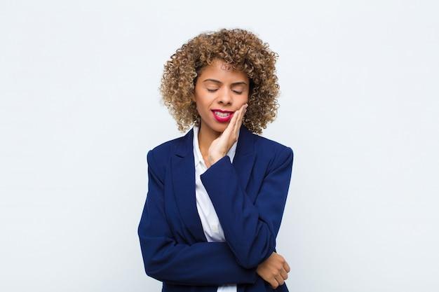Молодая женщина афроамериканец держит щеку и страдает от болезненной зубной боли, чувствует себя больным, несчастным и несчастным, ищет стоматолога у плоской стены