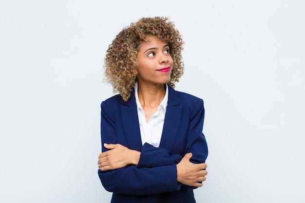 젊은 여자 아프리카 계 미국인 으 rug, 혼란과 불확실한 느낌, 팔을 의심하고 평평한 벽에 의아해 보인다