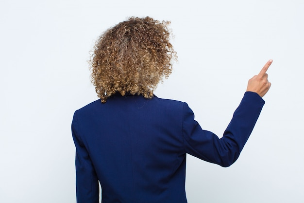 Young woman african american standing and pointing to object on copy space, rear view against flat wall