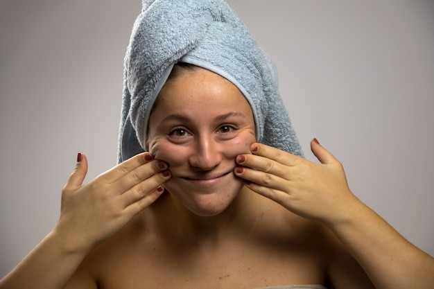 Young woman after shower with a towel and smiling. touching his face