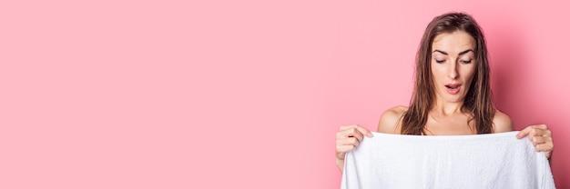 Молодая женщина после спа-процедур с удивлением смотрит на себя, прикрывшись полотенцем на розовом фоне.