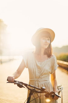 Young woman against nature background with bike