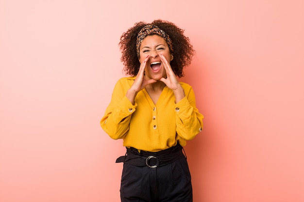 Young woman against a pink wall shouting excited to front
