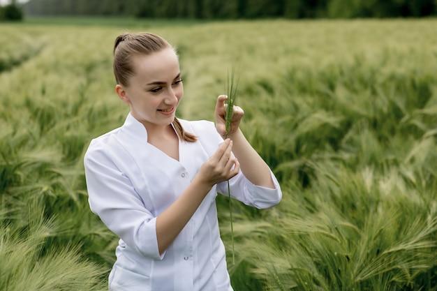 Молодая женщина-агроном в белом халате сидит на корточках в зеленом пшеничном поле и проверяет качество урожая.