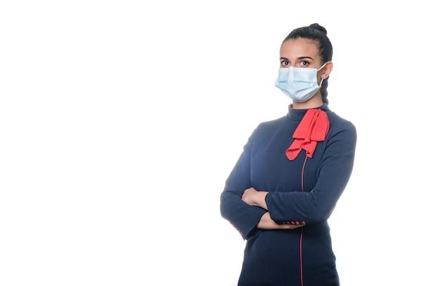 コロナウイルスのパンデミックを防ぐためにフェイスマスクを身に着けている制服を着た若い女性のスチュワーデス