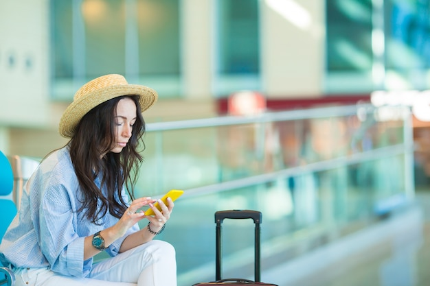 Young woman in an airport lounge waiting for flight aircraft.