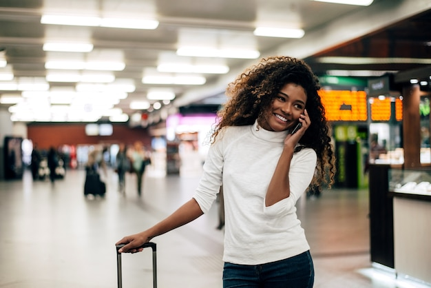 Young woman at the airport with trolley bag, talking on the phone.