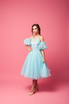 A young woman in an airy dress with sleeves and beige shoes poses against an isolated background a b...