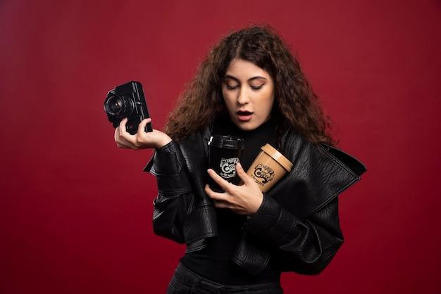 Giovane donna in abito tutto nero che tiene una tazza e una macchina fotografica.
