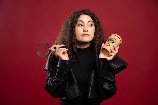 Giovane donna in abito tutto nero che tiene una tazza con la lente di ingrandimento.