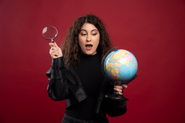 Young woman in all black outfit holding a globe with loupe.