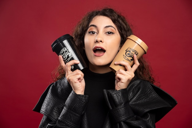 Giovane donna in abito tutto nero che tiene due tazze.