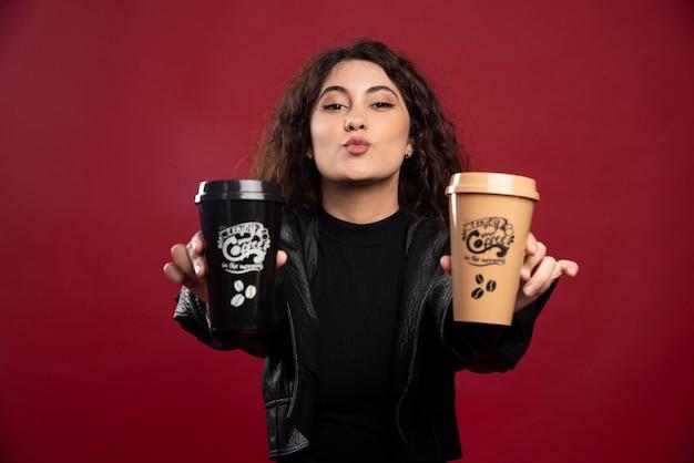 Giovane donna in abito tutto nero che mostra due tazze.