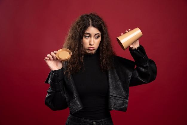 Giovane donna in abito tutto nero con la tazza vuota aperta.