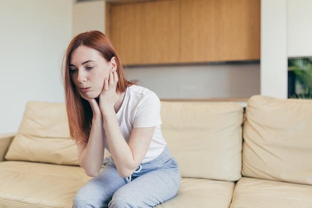 Молодая женщина одна дома с приступом паники, одышкой, дрожью, онемением, потерей сознания. вид спереди женщины, страдающей тревогой, сидя на диване. боль в груди, симптом страха