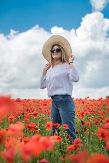 フィールド夏の日にポピーで一人で若い女性