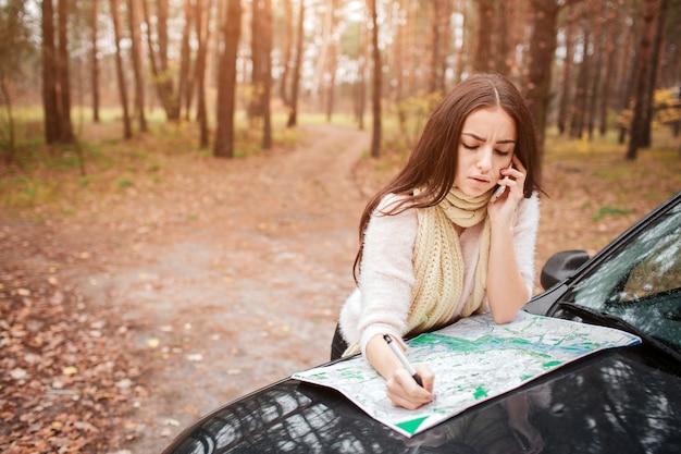 젊은 여자 혼자 자동차 여행자지도 함께. 손을 닫습니다. 가 컨셉입니다. 차로 가을 숲 여행