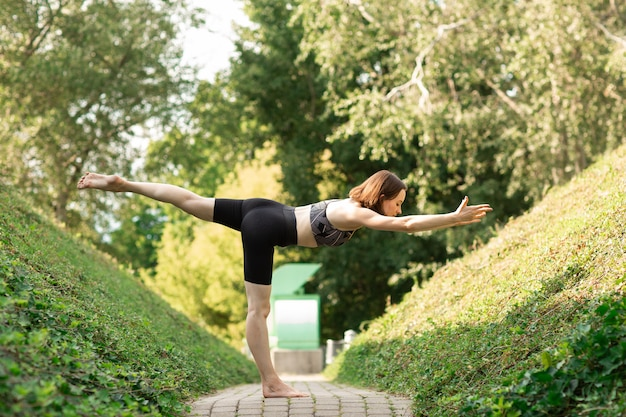 Young woman alone doing yoga on a park alley on a sunny summer day.