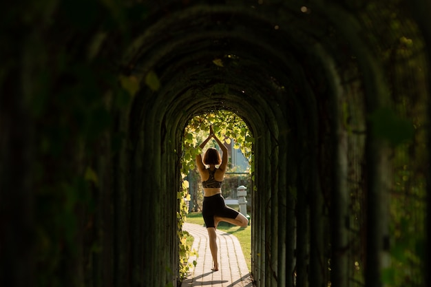 Young woman alone doing yoga on a sunny summer day.