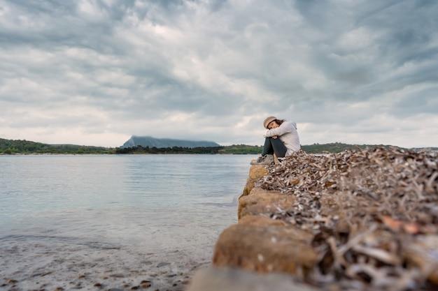 일몰 극적인 하늘과 바다에 오래 된 돌 부두에 혼자 젊은 여자