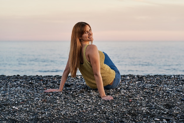 Young woman alone sitting on beach sand at sunset. concept of relaxation and meditation