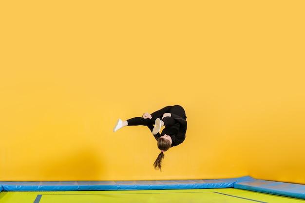 Молодая женщина-спортсмен-любитель акробатика прыгает и тренируется на батуте в помещении, современное хобби