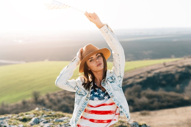 Young woman in american flag t-shirt on top of mountain