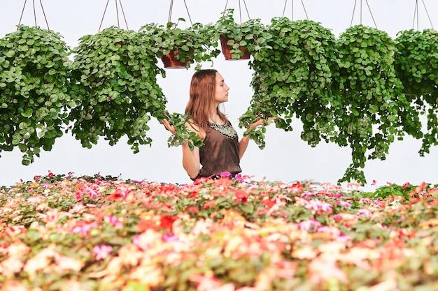 꽃들 사이에 있는 젊은 여성과 밝은 배경의 화분에 실내 식물을 매달고
