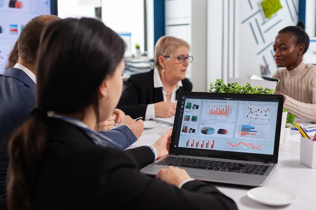 スタートアップのビジネス会議室でラップトップのチャートを分析する若い女性。多民族の同僚がチームの多様な人々のリーダーシップをブリーフィングします。上級管理職を聞いているアフリカの従業員。