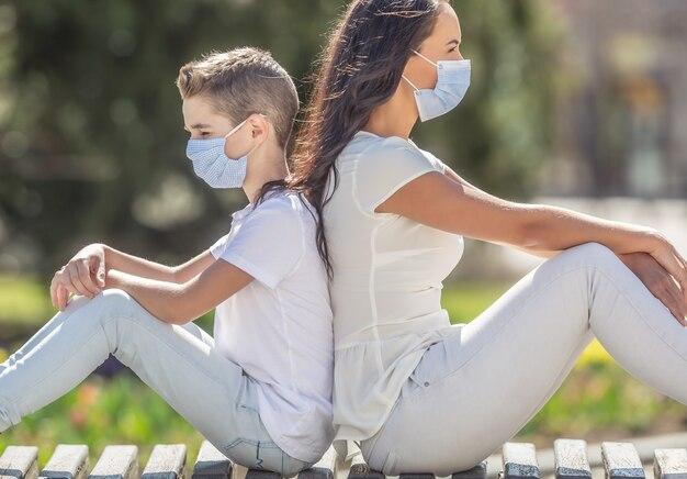 若い女性と男の子は、街のベンチに背中合わせに座って、薄手の服を着て、顔に1回限りのフェイスマスクを付けています。