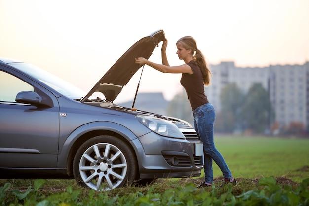젊은 여자와 터진 후드와 함께 차. 운송, 차량 문제 및 고장 개념.