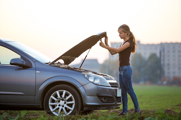 젊은 여자와 터진 후드가 있는 자동차. 교통, 차량 문제 및 고장 개념.