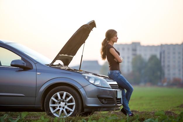 Молодая женщина и машина с приоткрытым капотом. транспорт, проблемы с транспортными средствами и концепция поломок.